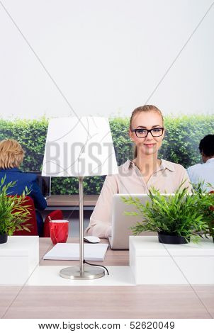Portrait of beautiful environmentalist sitting at desk in office