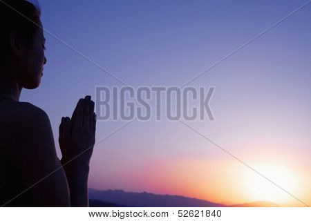Serene young woman with hands together in prayer pose in the desert in China