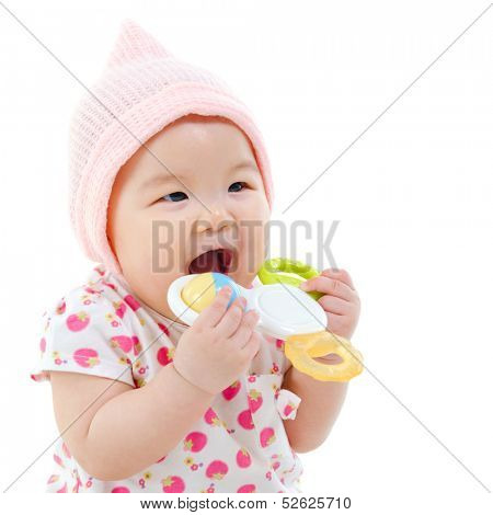 Beautiful mixed race Asian baby girl teething, biting with her toys, isolated on white background.