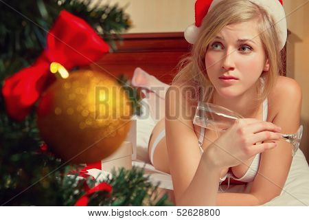 Young woman in Santa's hats  with glass of champagne lying on bed remain all alone