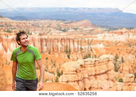 Hiker - man hiking in Bryce Canyon national park. Happy male outdoorsman walking enjoying outdoor activity walking in beautiful nature landscape in Utah, USA. poster