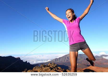 Success winner fitness runner woman jumping happy, excited and energetic with happy cheering face expression celebrating. Sporty running girl cheering after training outdoor in volcano landscape. poster