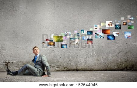 Image of young man sitting on floor looking at photos