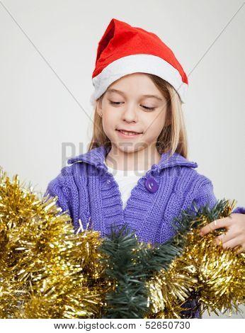 Smiling girl in Santa hat looking at tinsels at home during Christmas