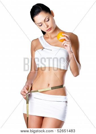 Girl Measures Figure With A Measuring Tape And Holding Orange