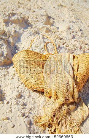 female handbag of straw on sand