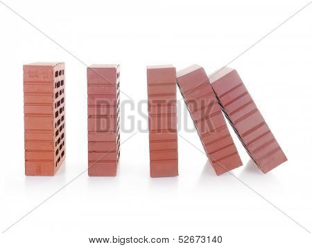 Line of red bricks with the first brick falling over the next one making a domino effect shot over white