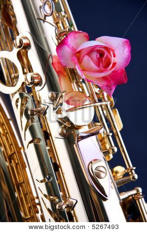 Saxophone And Pink Rose On Blue