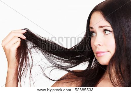 brunette woman is not happy with her fragile hair, white background, copyspace