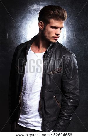 side view of a serious young fashion model in leather jacket looking away from the camera