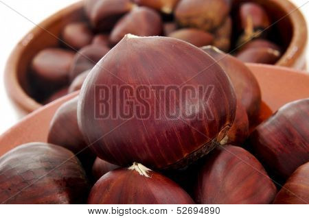 closeup of some chestnuts in earthenware bowls on a white background