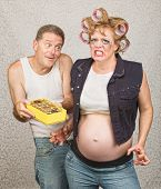 Angry pregnant woman in curlers with candy and man poster