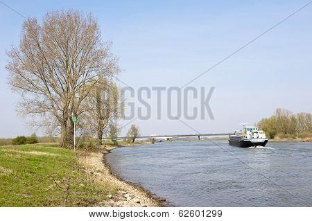 Cargo Ship On River In Rural Scenery
