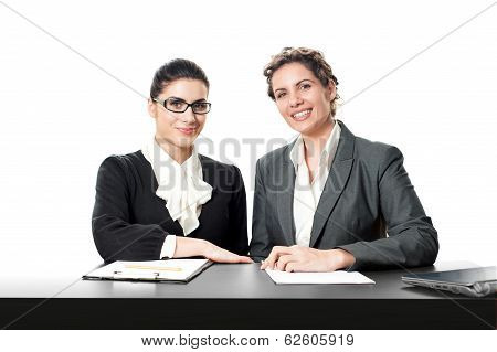Two young beautiful businesswoman sitting at frontdesk