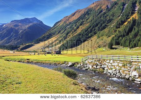 National Park Krimml Waterfalls in Austria. Headwaters of waterfalls - a narrow fast roiling river among green mountain meadows