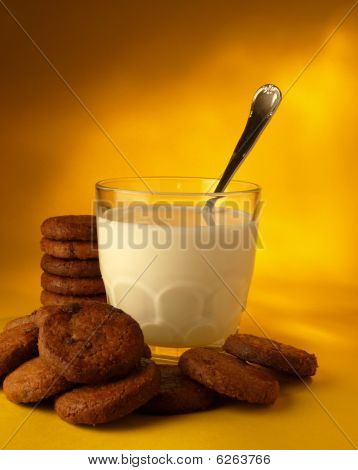 Milk glass accompanied by chocolate chip cookies