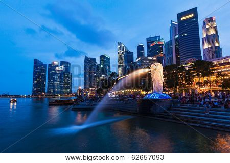 SINGAPORE - JANUARY 1, 2014: Night view of Singapore Merlion at Marina Bay against Singapore skyline. Merlion is a well-known tourist icon, mascot and national personification of Singapore