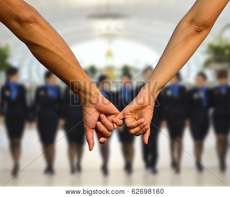 Hand In Hand Together As A Good Teamwork With Woman In Uniform In Background
