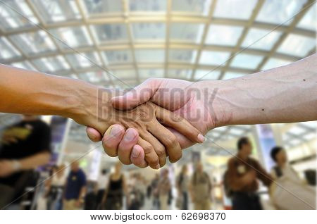 Handshaking As Promise To Provide Best Service Quality In Front Of Happy Walking People In Backgroun