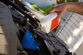 A backyard mechanic pours motor oil into the engine at the end of an oil change. Home maintenance is becoming more popular during hard economic times. poster