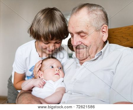 Great Grandfather Holding A New Born Baby Girl Next To His School Age Grandson