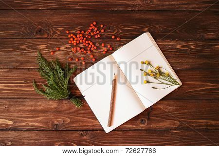 Blank white notebook, wooden pencil and ashberry on wooden background