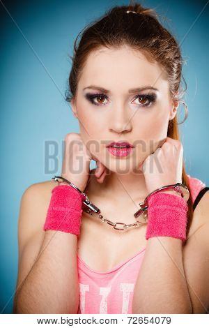 Teen crime arrest and jail - Criminal teenager girl prisoner woman in handcuffs blue background poster