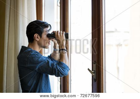 Man Looking Through A Glass Door With Binoculars