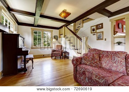 Family Room With Antique Piano And Comfortable Red Sofa