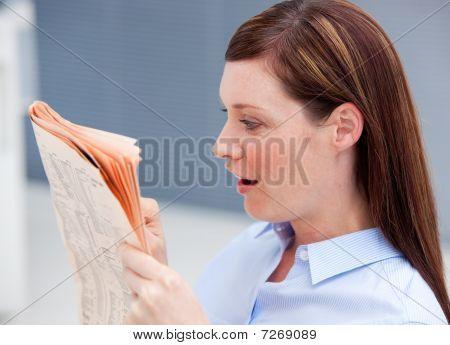 Surprised Businesswoman Reading Newspaper