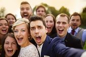 Young couple of newlyweds with group of their firends taking selfie and making funny grimaces poster