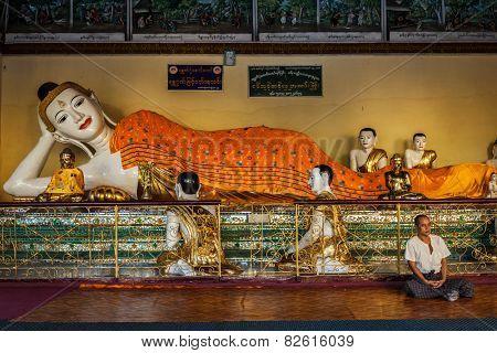 YANGON, MYANMAR - JANUARY 3, 2014: Man meditating near statue of Recumbent Buddha in Shwedagon Paya pagoda