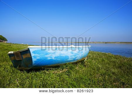 small boat laying on the grass at the shore of river Somme Normandy France poster