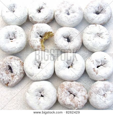 A background of powdered sugar dough-nuts with a bite out. poster