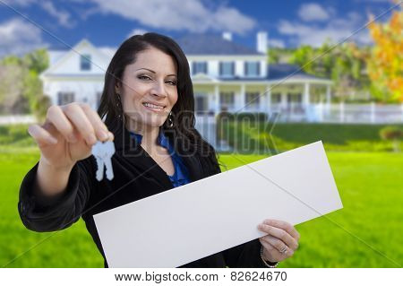 Hispanic Woman Holding Blank Sign and Keys In Front of Beautiful House.