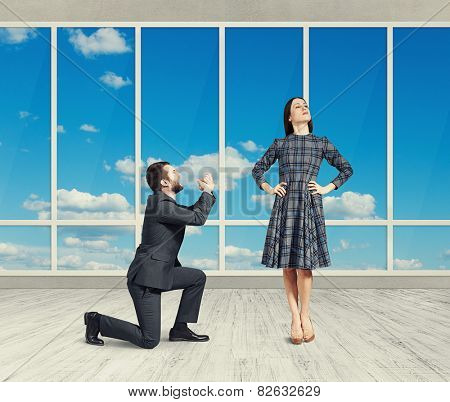 sad man looking at young attractive woman and asking for forgiveness. photo in empty room with big windows