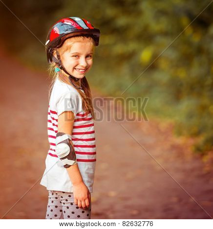 happy little girl on roller skates in the autumn forest close-up