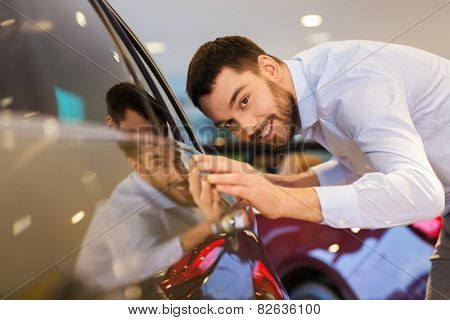 auto business, car sale, consumerism and people concept - happy man touching car in auto show or salon