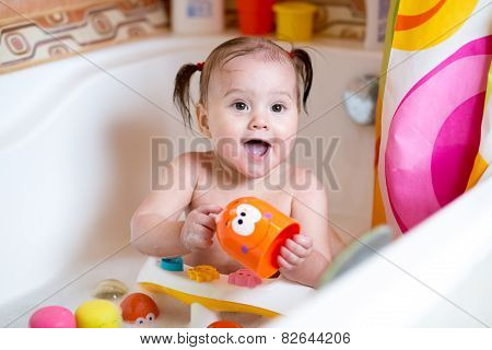 funny baby smiling while taking a bath
