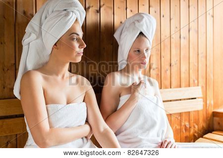 Two Women in wellness spa relaxing in wooden sauna