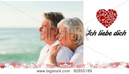 Woman hugging her husband at the beach against ich liebe dich