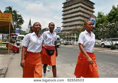 Four Black African Women In Uniform, Orange Skirts And White Shirt.