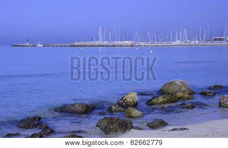 Morning in the Can Pastilla marina rocks on sandy beach blue Mediterranean and white masts as the sun rises Majorca Spain. poster