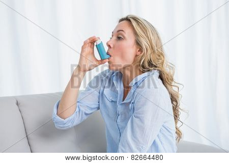 Blonde using her asthma inhaler on couch at home in the living room