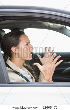 Young woman experiencing road rage in her car