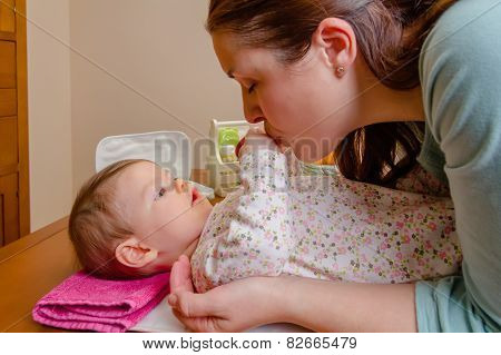 Mother kissing hands of her baby lying