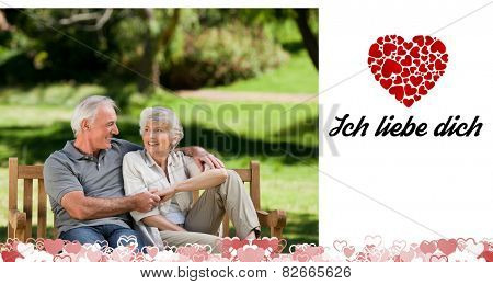 Senior couple sitting on a bench against ich liebe dich