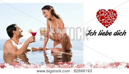 Couple having cocktails in the pool against ich liebe dich