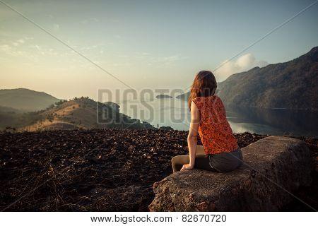 Woman Sitting On Unusual Rock At Sunrise