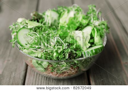 Cress salad with sliced cucumber and greens in glass bowl on wooden planks background